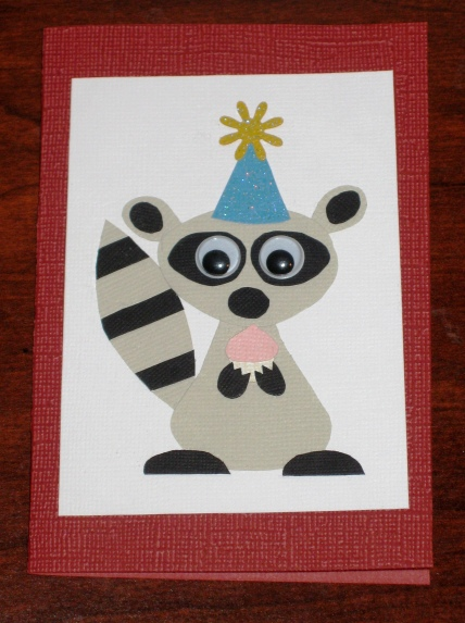 A card of a raccoon holding a birthday cupcake
